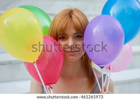 Portrait of a white girl with orange hair sitting on a white stairs holding colorful balloons with their hands.