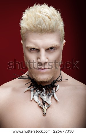 Portrait of a white man with a bone necklace on a red background - stock photo