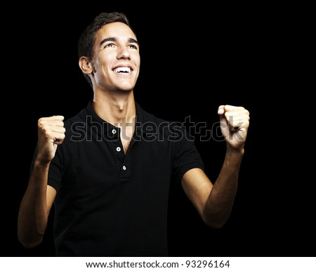 portrait of a winner young man looking up over a black background - stock photo