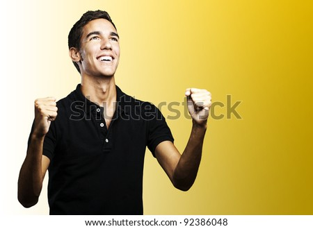 portrait of a winner young man looking up over yellow background - stock photo
