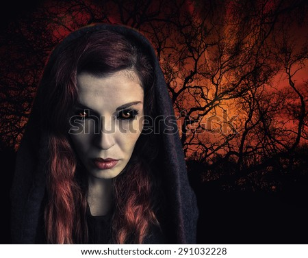 Portrait of a witch with scary eyes and a wood on fire in background. - stock photo