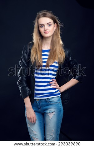 Portrait of a woman. A woman in a leather jacket standing on a dark background photo studio. Space for text. Sailor girl. Beautiful sad woman. - stock photo