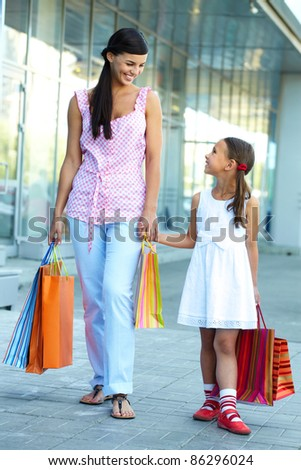Portrait of a woman and girl walking with shopping bags - stock photo