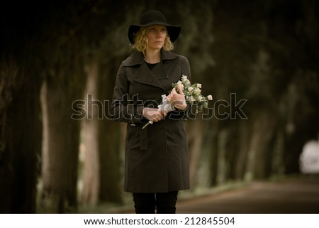 Portrait of a woman at cemetery holding flowers - stock photo