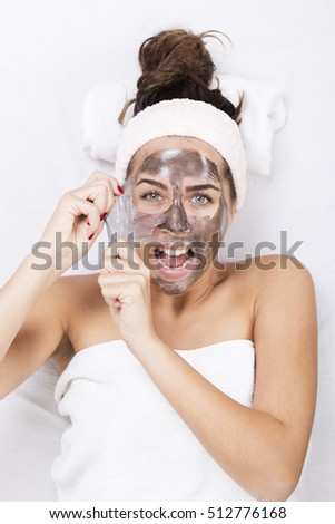 Portrait of a woman at the spa, screaming during the removing the mask from the face