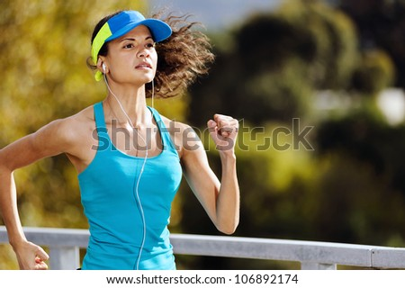 Portrait of a woman athlete runner training outdoors with cap and headphones listening to music. endurance sport. - stock photo