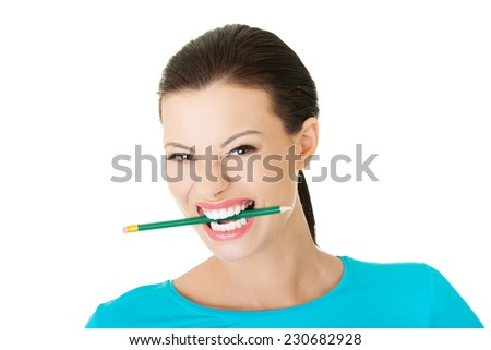 Portrait of a woman biting her pencil. - stock photo