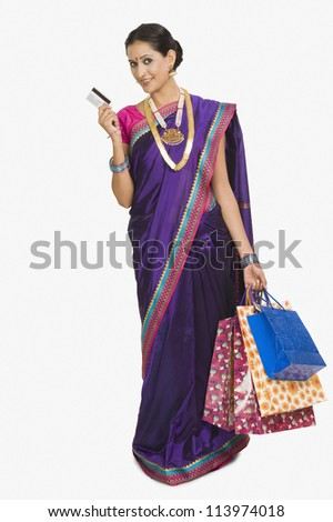 Portrait of a woman carrying shopping bags and a credit card - stock photo