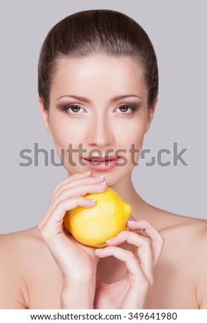 Portrait of a woman close up woman looks directly into the camera,her face make-up day with light texture pastel tones in her thin hands slender yellow lemon she holds it in front of you near the face