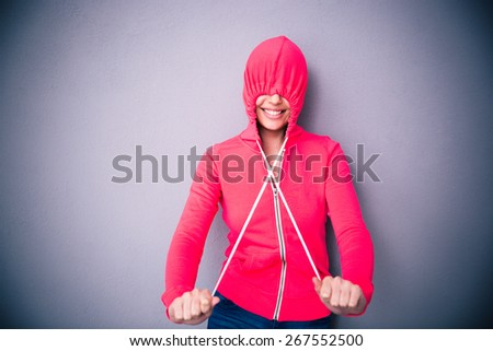 Portrait of a woman covering her eyes with hood over gray background - stock photo