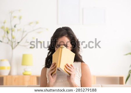 Portrait of a woman covering her face with a book - stock photo