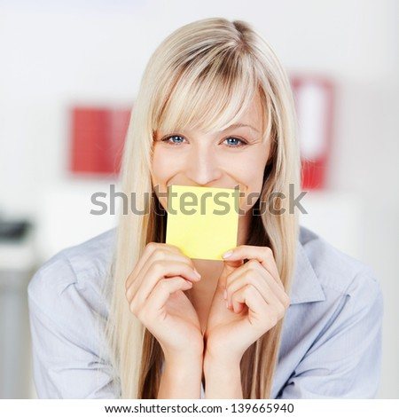Portrait of a woman covering her mouth using a yellow empty sticky note