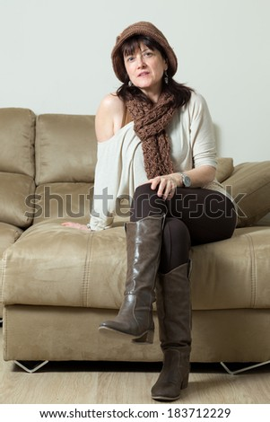 Portrait Of A Woman Dressed In Hat, Scarf And Boots, Sitting On The Sofa