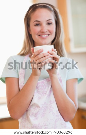 Portrait of a woman drinking a cup of coffee in her kitchen