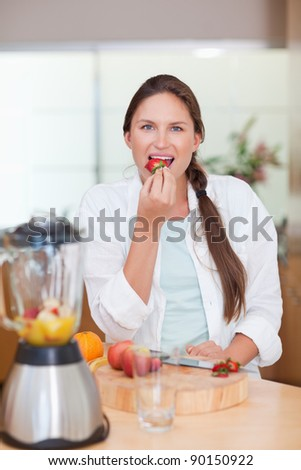 Portrait of a woman eating a strawberry in her kitchen - stock photo