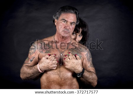 Portrait Of A Woman Embracing A Man With Tattoo From Behind