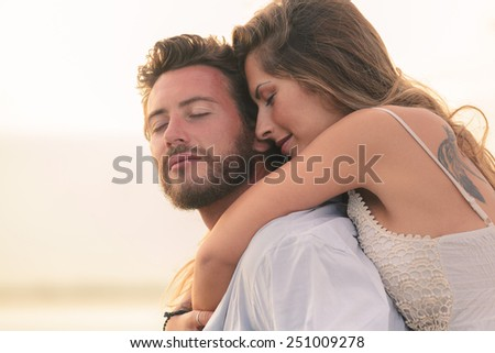Portrait of a woman embracing her man from behind on sunset background - stock photo
