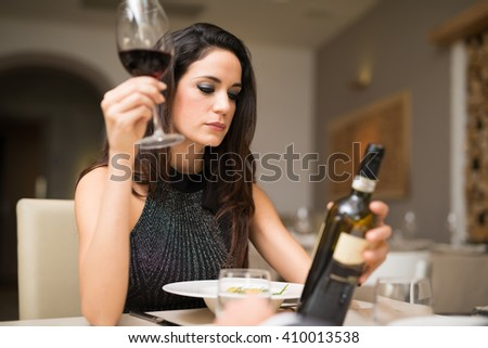 Portrait of a woman enjoying a glass of red wine in a restaurant - stock photo
