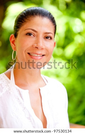 Portrait of a woman enjoying nature outdoors and smiling - stock photo
