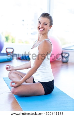 Portrait of a woman happy woman doing meditation in fitness studio - stock photo