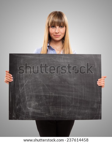 Portrait of a woman holding a blackboard - stock photo
