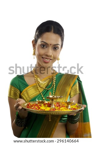 Portrait of a woman holding a tray with diyas