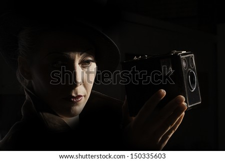 Portrait of a woman holding an old box camera in the style of 1930s film noir.