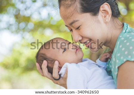 Portrait of a Woman holding her baby girl outdoor