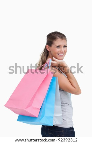 Portrait of a woman holding shopping bags against a white background