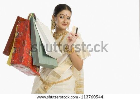 Portrait of a woman holding shopping bags with a credit card - stock photo