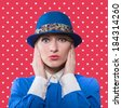 Portrait of a woman in a blue hat with hands holding her face, red polka dot background - stock photo