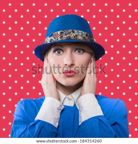 Portrait of a woman in a blue hat with hands holding her face, red polka dot background