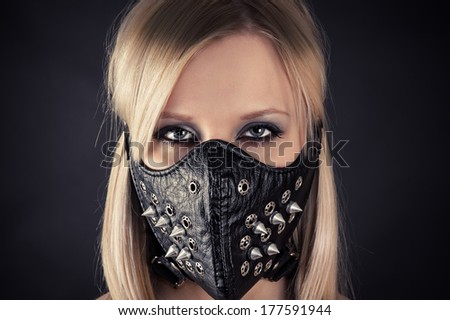 portrait of a woman in a mask with spikes - stock photo