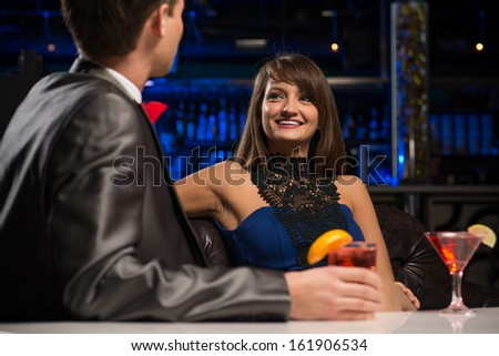 portrait of a woman in a nightclub, sitting on the couch and talking with man