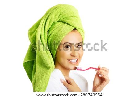 Portrait of a woman in bathrobe brushing teeth. - stock photo