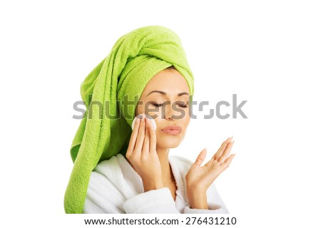 Portrait of a woman in bathrobe removing makeup. - stock photo
