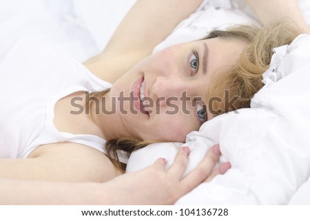 Portrait of a woman in bed looking at camera