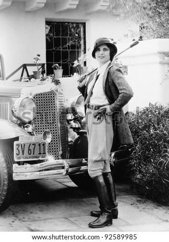 Portrait of a woman in front of her car in a riding outfit - stock photo