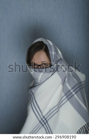 Portrait of a woman in glasses hiding her face and head under veil or plaid, vertical studio shot - stock photo