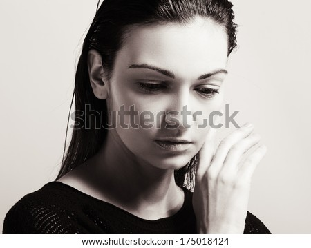 portrait of a woman in pain, frowning with hand on head