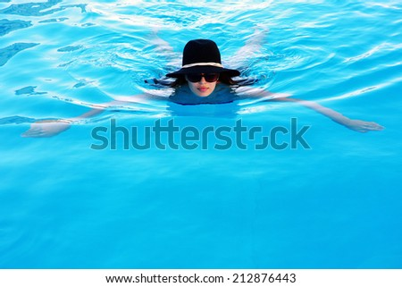 Portrait of a woman in sunglasses and hat swimming in the pool