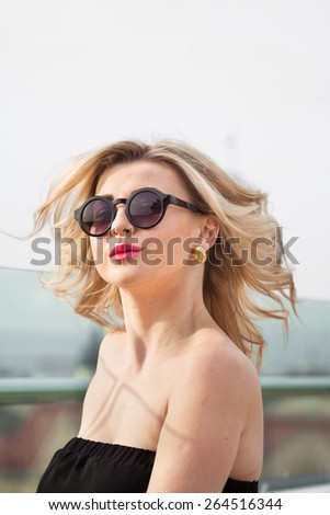 portrait of a woman in sunglasses in black dress in the city