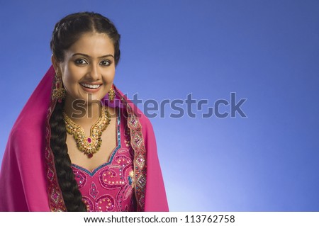 Portrait of a woman in traditional dress and smiling - stock photo