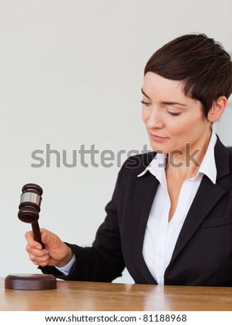 Portrait of a woman knocking a gavel against a white background - stock photo