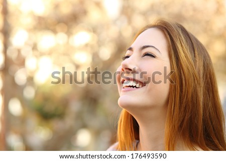 Portrait of a woman laughing with a perfect teeth on a warmth background              - stock photo