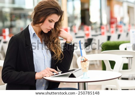 Portrait of a woman looking at her tablet computer, sitting in a coffee shop - stock photo