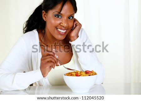 Portrait of a woman looking at you and eating a bowl of cereals with strawberries at soft colors composition. with copyspace - stock photo