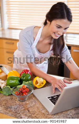Portrait of a woman looking for a recipe on the internet in her kitchen - stock photo