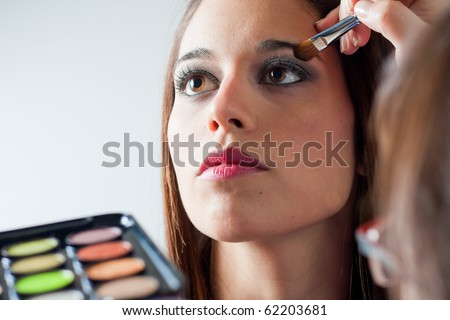 Portrait of a woman making up eyes - stock photo
