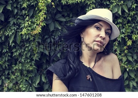Portrait of a woman near the wall with leaves